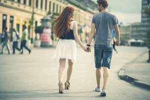 Rear view of young ginger couple walking in the street while holding hands.