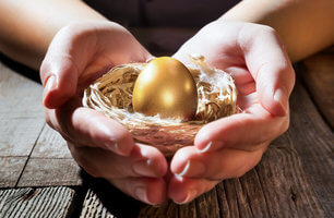 Hands holding golden egg in a birds nest